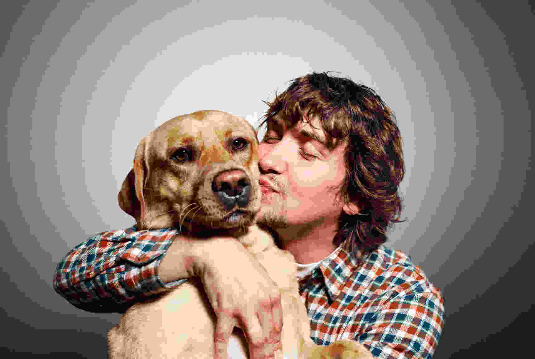 blurry compressed image of man kissing dog
